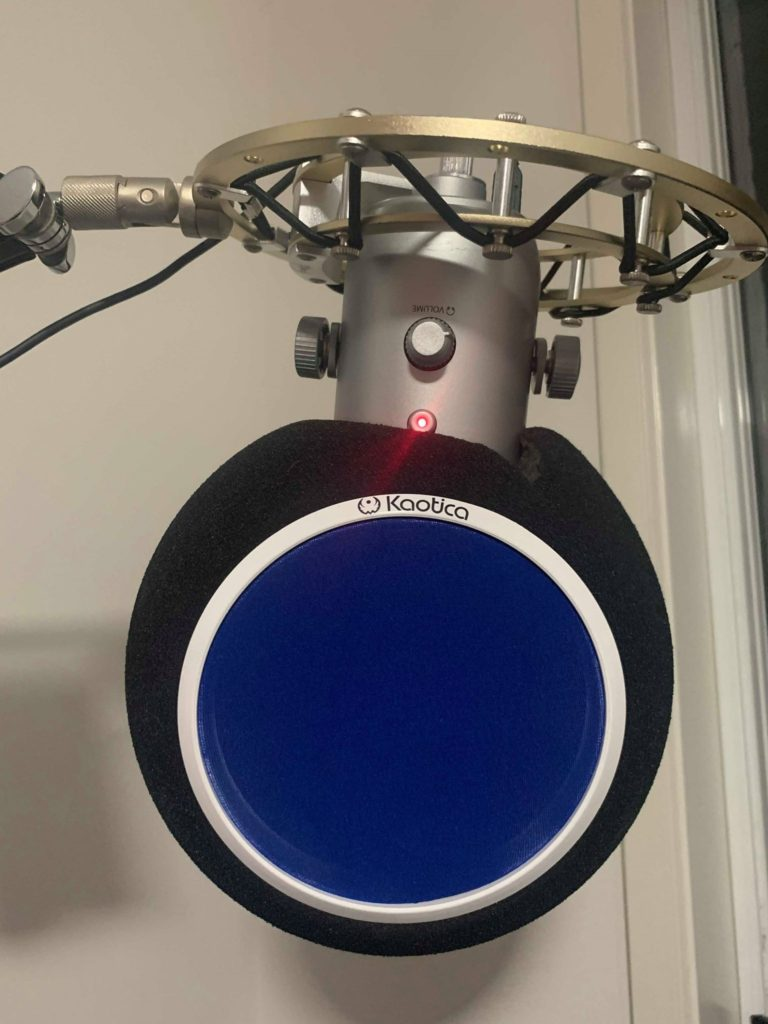 A silver blue yeti brand mic hanging from a boom arm with a black foam eyeball and blue pop filter