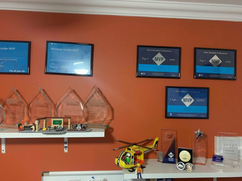 An orange wall with Microsoft MVP certificates and white shelves with glass trophies.
